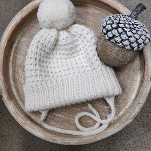 Earflap baby hat with a pompom